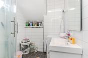 Badet i 1. etg. har fliser på gulv og baderomsplater på vegg