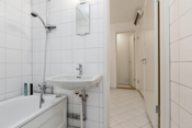 Badet har fliser på gulv og vegg. Innredet med badekar og vask.