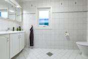 Badet har installert dusjkabinett, servant med underskap, høyskap og toalett