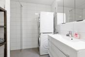 Badet har flott baderomsinnredning, dusjhjørne, toalett og opplegg til vaskemaskin