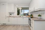 Pent kjøkken med integrerte hvitevarer som koketopp, stekeovn, oppvaskmaskin og kombinert kjøl- og fryseskap