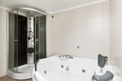 Flislagt bad i kjeller med boblebadekar og dusjkabinett