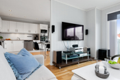 En kort vegg skiller naturlig kjøkken og stue - prakisk som tv-vegg