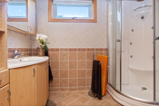 Flislagt bad med dusjkabinett, wc og baderomsinnredning