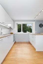 Naturlig skille mellom kjøkken og stue med kjøkkeny med barløsning