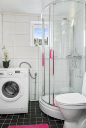 Badet har dusjkabinett, wc, innredning og opplegg til vaskemaskin
