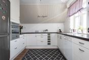 Kjøkken i 2. etasje med oppvaskmaskin, integrert komfyr, platetopp og ventilator.
