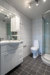 Badet er innredet med toalett, dusjkabinett, innredning med servant og opplegg til vaskemaskin.