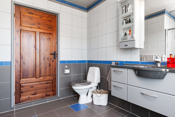 Badet har stor dusjnisje, toalett og baderomsinnredning