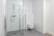 Flislagt bad med vegghengt toalett og dusjhjørne