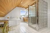 Badet i 2. etasje - flislagt med dusj i nisje av glassbyggersten