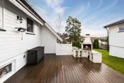Stor terrasse med plass til stort spisebord ved utepeisen