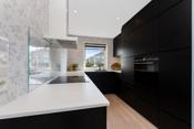 Herdet glassplate over stekeplate gir et stilfullt preg til kjøkkenet.