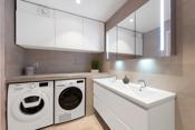 Praktisk dobbelvask. Overskap med speil og ekstra oppbevaring i skapet, som har lys både utvendig og innvendig. God benkeplass for alle slags praktiske formål.