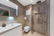 Badet inneholder praktiske dusjvegger som er kan skyves inn til veggen og dermed frigjøre plass på badet.