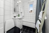 Bad med toalett, servant og badekar. Det er opplegg for vaskemaskin bak badekar iht. opplysninger gitt av eier.