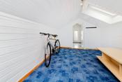For øvrig disponerer boligen innredet loft med to oppholdsrom. Det er teppe på gulvet og malt panel på veggene.
