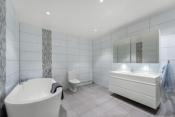 Stort flislagt bad med varmekabler og badekar.