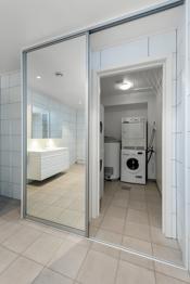 Inngang til vaskerom fra badet gjennom skyvedørsgarderoben.