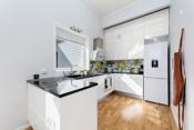 Kjøkkeninnredning med hvite glatte flater og granitt benkeplate.