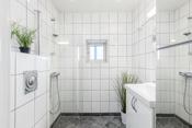 Lyst flislagt bad med dusj og wc - varmekabler i gulv.