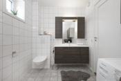 Flislagt bad i 2.etasje med gulvvarme, badet inneholder veggmontert klosett med innbygget sisterne, dusjnisje og servantskap med hel servantplate. Røropplegg for vaskemaskin.