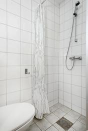 Badet er moderne og inneholder veggmontert klosett med innbygget sisterne, dusjnisje og servantskap.