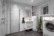 Baderommet i 1.etasje har pene fliser på gulv og vegger. Rommet fungerer som en fin kombinasjon mellom bad og vaskerom med opplegg for vaskemaskin.