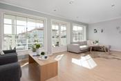 Stuen er lys og åpen med store vindusflater som gir rommet rikelig med naturlig lys.