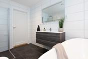 Baderommet har en fin størrelse og inneholder veggmontert klosett med innbygget sisterne, servantskap med blandebatteri, dusjnisje med nisjedører i glass, og et deilig badekar.