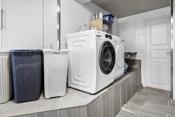 Vaskerom med opplegg for vaskemaskin. Varmepumpe. Innredning/benkeplate og rikelig med oppbevaring.