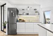 Integrert komfyr, platetopp og oppvaskmaskin. Skiferstaver mellom benkeplater og overskap. Innredningen er fra 2016.