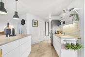 Kjøkkeninnredning med hvite glatte fronter. Kjøkkenøy. Laminerte benkeplater.