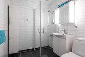 Badet er innredet med dusjhjørne, toalett og innredning med servant.