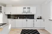Nymalt kjøkkeninnredning med plater over benk