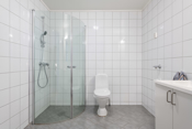 Bad med innredning med servant, toalett, dusjhjørne og opplegg til vaskemaskin.