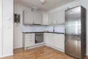 Kjøkken med integrert komfyr, platetopp, oppvaskmaskin og ventilator.