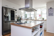 Delikat kjøkken med integrerte hvitevarer og øy