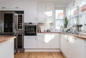 Kjøkken med integrerte hvitevarer som bl.a vinskap og side by side kjøl/frys med isbitter
