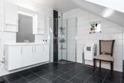 Badet er innredet med veggtoalett, dusj og innredning med servant.