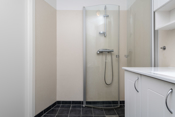 Badet er innredet med toalett, dusjhjørne, innredning med servant og opplegg til vaskemaskin.