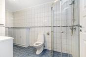 Badet er innredet med dusjhjørne, toalett. servant, ekstra skap og nisje for vaskemaskin