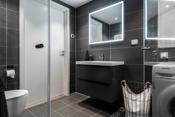 Flott bad med vegghengt toalett, innredning og integrert lys i speil