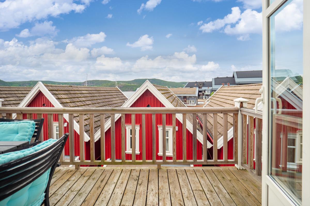 I forkant av hytten ligger sjarmerende sjøboder - Fra balkongen ser man mot fjorden