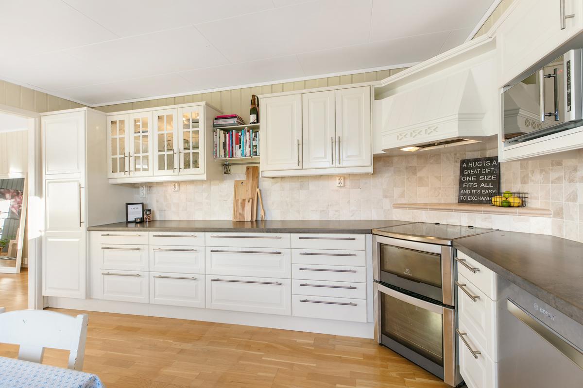 Stort kjøkken med lys profilert innredning. Bra med benke og skapplass.