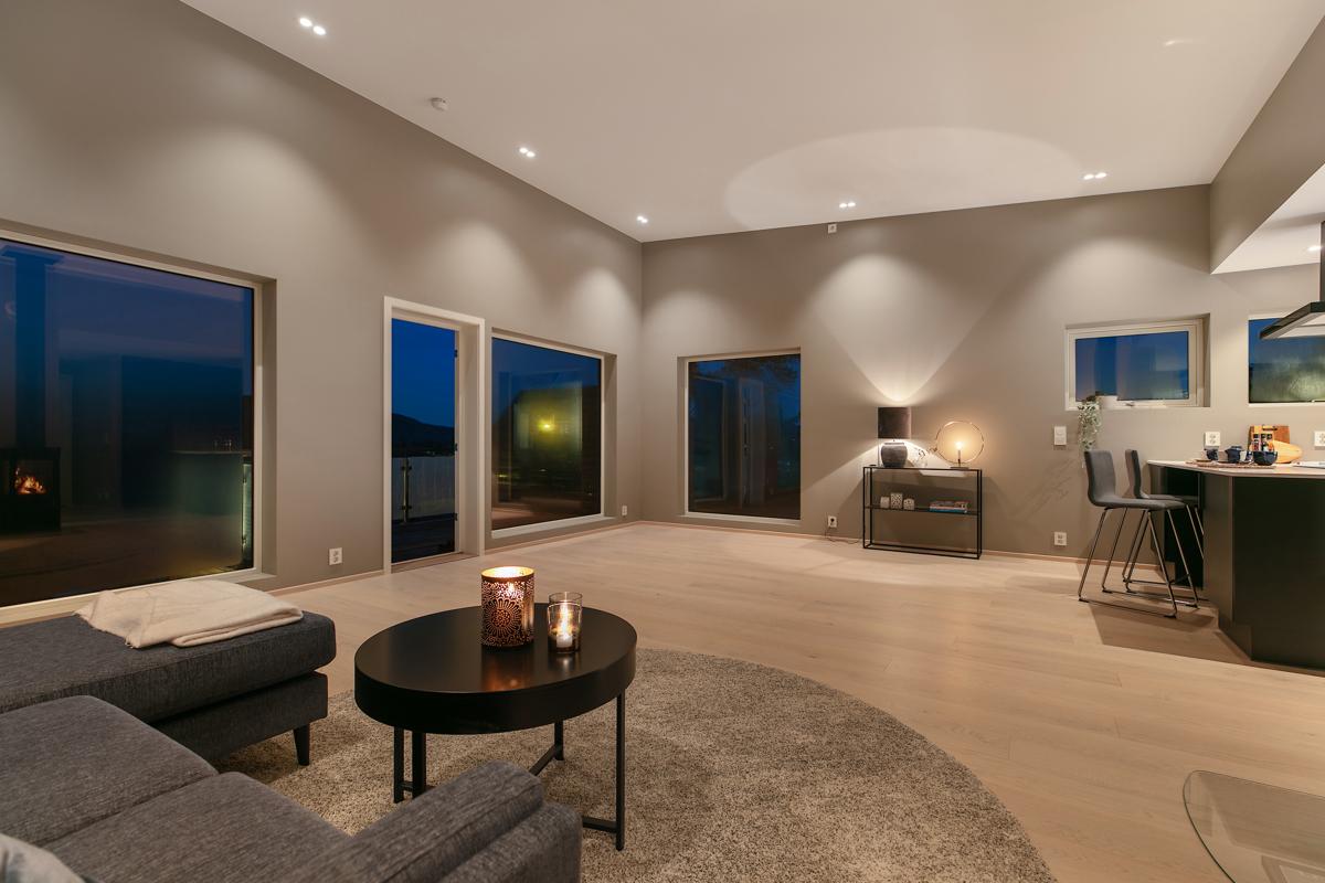 Moderne innredet stue med delikate farger - downlights i tak - parkett på gulv.
