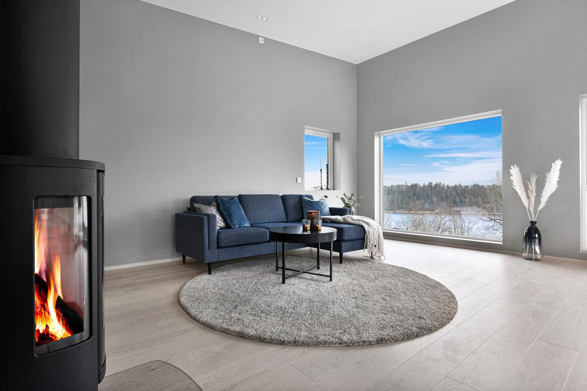 Store vinduer i stue som gir mye lys inn. Utsikt til sjøen kan nytes fra sofaen.