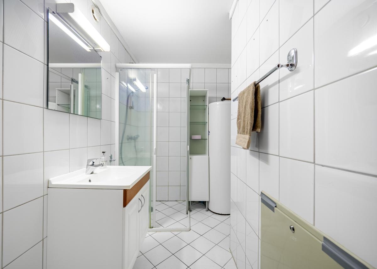 Bad med servantinnredning, dusjhjørne og opplegg til vaskemaskin
