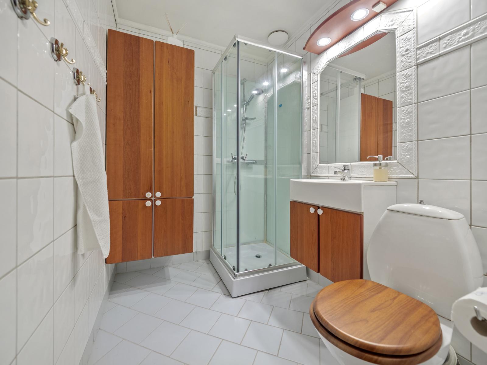 Bad med dusjkabinett, wc og servant.