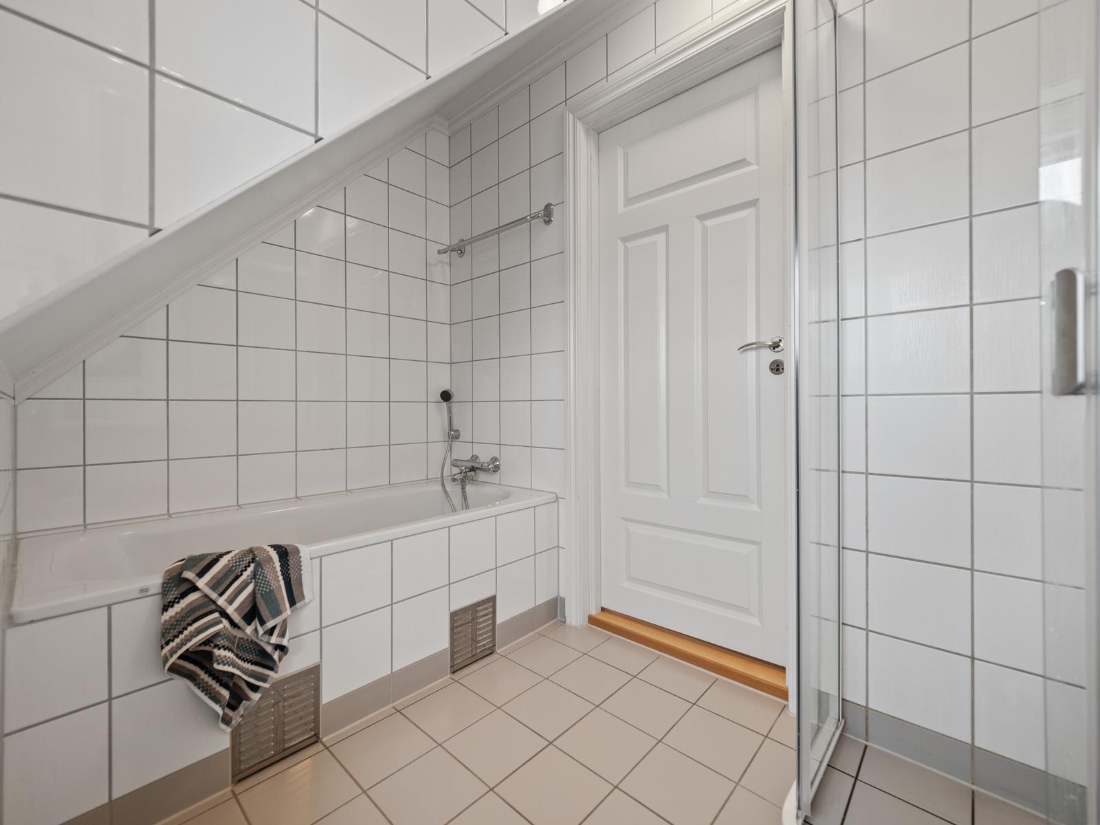 Badet i 2.etg. er innredet med vegghengt toalett, dusjhjørne, søylevask og badekar.
